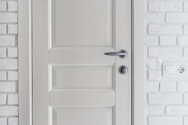 Klasyczne drzwi i ściany ozdobione dekoracyjną cegłą. białe skandynawskie wnętrze