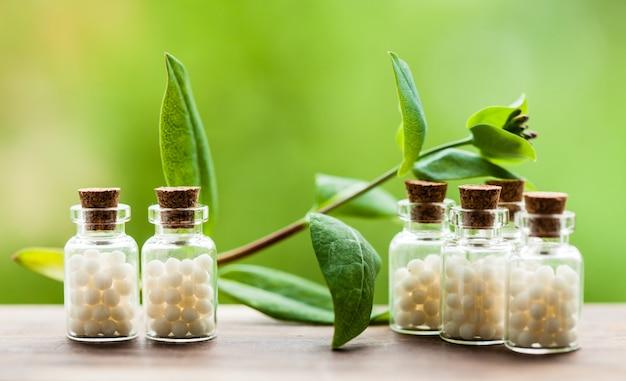 Klasyczne globulki homeopatii w starych butelkach i liściach natury