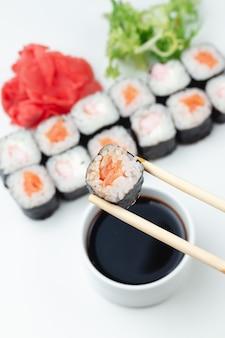 Klasyczne japońskie sushi rolki na jasnym tle