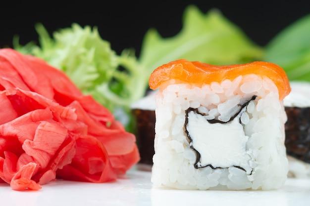 Klasyczne japońskie sushi rolki w zbliżeniu na ciemnym tle