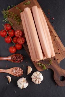Klasyczne kiełbaski wieprzowe gotowane na desce do krojenia z papryką i bazylią, pietruszką, tymiankiem i pomidorkami koktajlowymi.