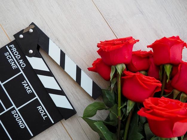 Klasyczne klasyczne clapperboard na brązowym drewnianym stole szepczą czerwone róże.