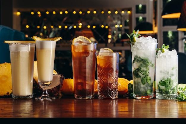 Klasyczne koktajle long drink na stole mojito long island i pina colada
