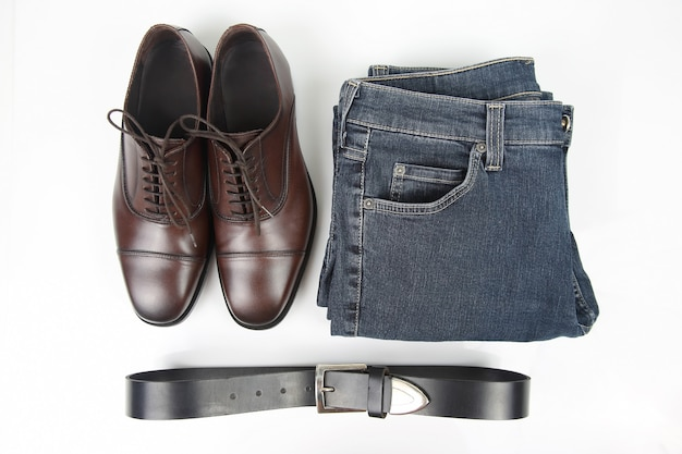 Klasyczne męskie brązowe buty, pasek i ubrania na białej przestrzeni