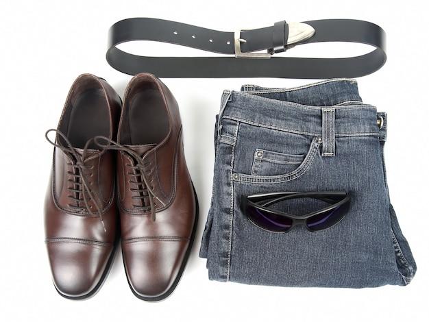 Klasyczne męskie brązowe buty, pasek i ubranie na białej powierzchni