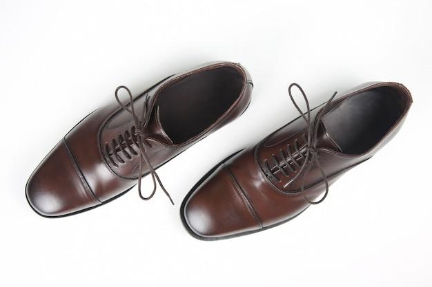 Klasyczne męskie buty oxford w kolorze brązowym na białym stole