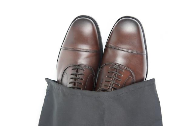 Klasyczne męskie buty oxford w kolorze brązowym w ochronnym czarnym etui na białej powierzchni