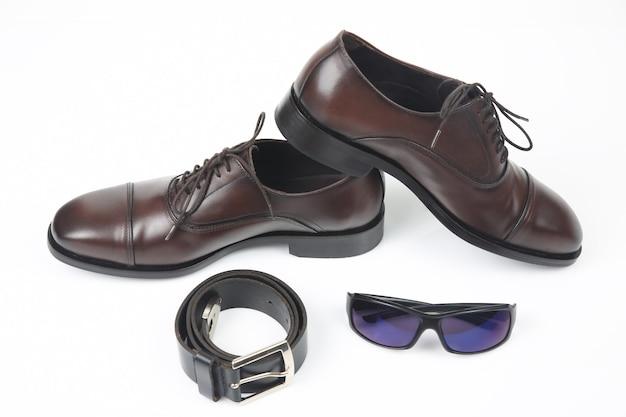 Klasyczne męskie buty, pasek i okulary na białym tle