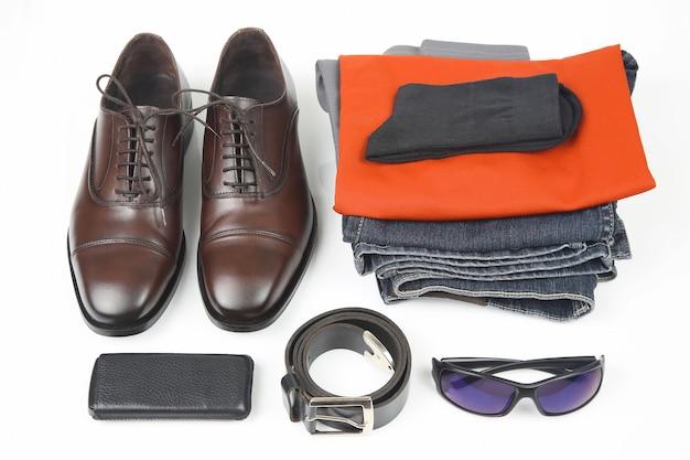 Klasyczne męskie buty, pasek, okulary, ubrania i telefon komórkowy na białym stole
