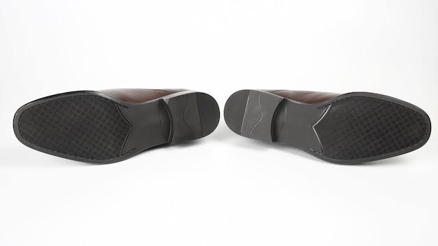 Klasyczne męskie buty z brązową podeszwą na białej przestrzeni
