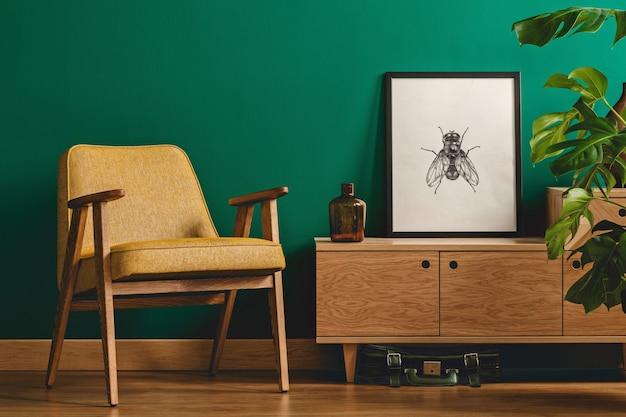 Klasyczne, minimalistyczne wnętrze salonu z oprawionym w ramkę plakatem z owadami na drewnianej komodzie, żółtym fotelu i roślinie monstera