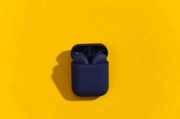 Klasyczne niebieskie słuchawki bezprzewodowe bluetooth lub wkładki douszne w etui ładującym na jasnożółtym tle.