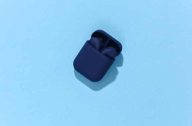 Klasyczne niebieskie słuchawki bezprzewodowe bluetooth lub wkładki douszne w etui ładującym