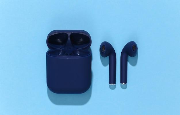Klasyczne niebieskie słuchawki bezprzewodowe bluetooth lub wkładki douszne z etui ładującym