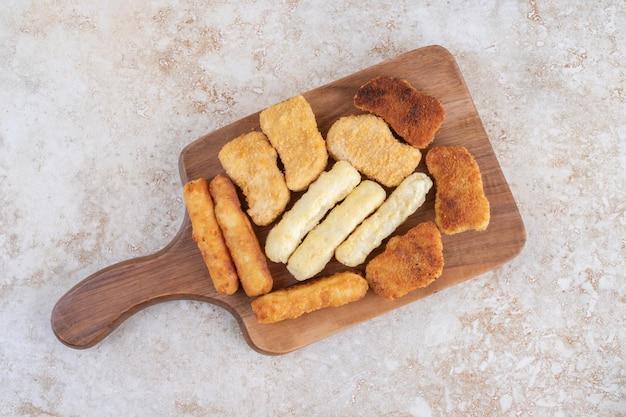 Klasyczne nuggetsy z kurczaka, kiełbaski i paluszki serowe na drewnianym półmisku.