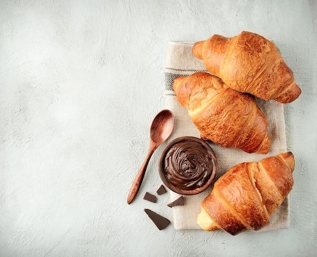 Klasyczne rogaliki z polewą czekoladową na betonowym stole. rogaliki z widokiem z góry. śniadanie.