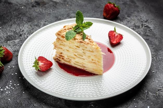 Klasyczne rosyjskie ciasto napoleon z kremem waniliowym ze śmietaną, jabłkami i konfiturą truskawkową zdobione miętą. baner, menu, miejsce na przepis na tekst, widok z góry
