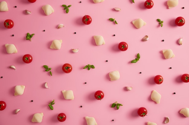 Klasyczne skorupki makaronu z pszenicy durum ze świeżymi pomidorami, zieloną bazylią, czosnkiem i pieprzem do przyrządzania smacznych dań kuchni włoskiej. tło żywności. niegotowany makaron z ziołami i warzywami. widok z góry, płaski układ