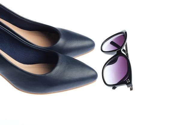 Klasyczne skórzane buty na wysokim obcasie i okulary przeciwsłoneczne na białym tle. akcesoria damskie