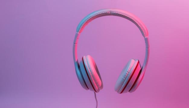 Klasyczne słuchawki przewodowe z gradientowym niebieskim różowym światłem neonowym. styl retro. minimalistyczna koncepcja muzyki.