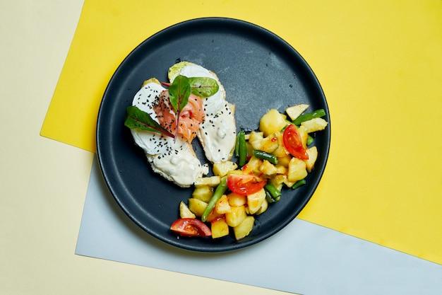 Klasyczne śniadanie kontynentalne - grzanki z twarogiem, łososiem i jajkiem w koszulce oraz przystawka z pieczonych ziemniaków z pomidorami na czarnym talerzu na s