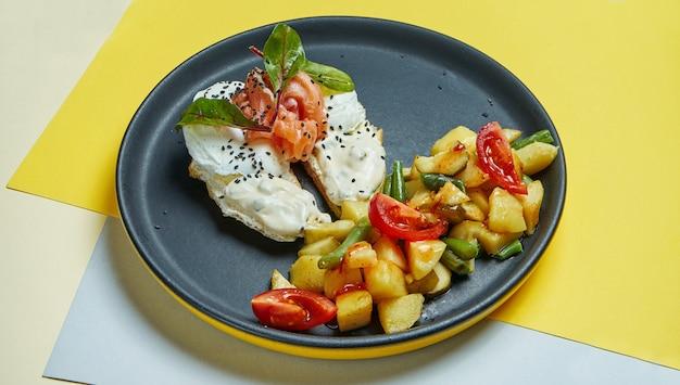 Klasyczne śniadanie kontynentalne - grzanki z twarogiem, łososiem i jajkiem w koszulce oraz przystawka z pieczonych ziemniaków z pomidorami na czarnym talerzu