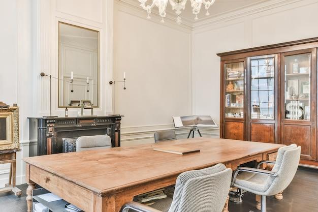 Klasyczne wnętrze dworu z drewnianym stołem i kredensem oraz kominkiem pod żyrandolem