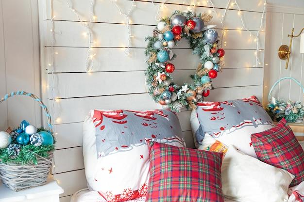 Klasyczne wnętrze pokoju z choinką i tradycyjnymi biało czerwonymi dekoracjami. nowoczesna, czysta biała sypialnia w stylu klasycznym. wigilia w domu. minimalistyczny projekt domu.
