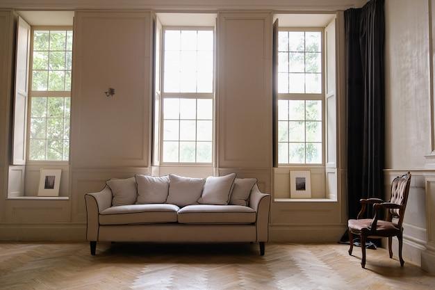 Klasyczne wnętrze z sofą, zabytkowym krzesłem i dużymi oknami.