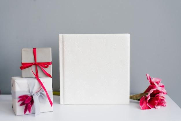 Klasyczny album ze zdjęciami w skórzanej białej okładce otoczonej pudełkami prezentowymi i różowym kwiatkiem na szaro