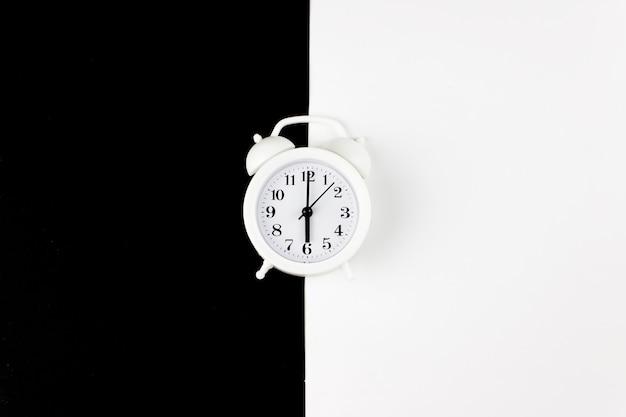 Klasyczny biały budzik na dwutonowym czarno-białym tle. widok z góry, miejsce na tekst.