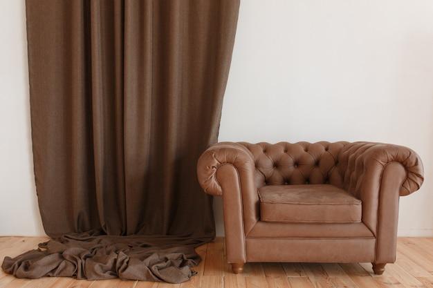 Klasyczny brązowy fotel tekstylny we wnętrzu z zasłoną i drewnianą podłogą