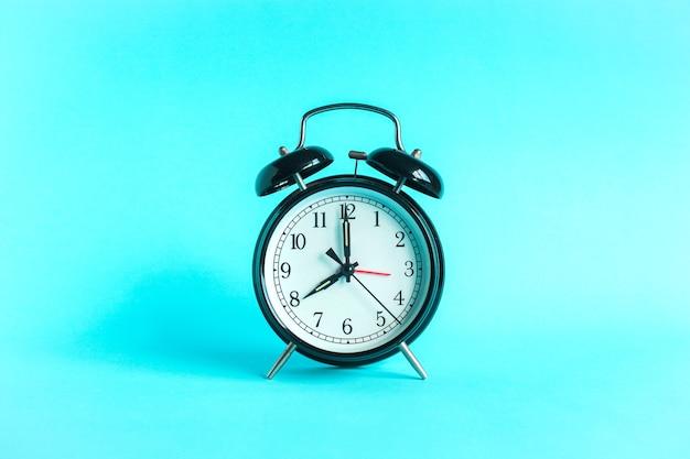 Klasyczny budzik wskazuje 8 godzin na białym tle na niebieskim tle