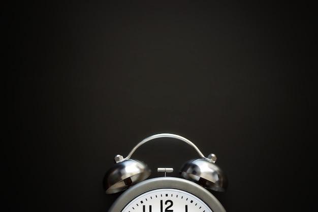 Klasyczny budzik z dzwoneczkami i strzałkami na powierzchni z czarnej tablicy