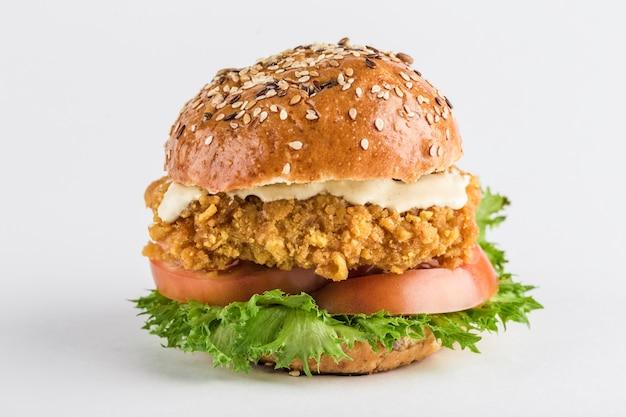 Klasyczny burger z kurczakiem w bułce z pomidorami sezamowymi, sałatą i sosem musztardowym.