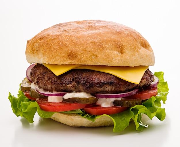 Klasyczny cheeseburger z sałatką, pomidorem i kiszonymi ogórkami na białym tle. odosobniony