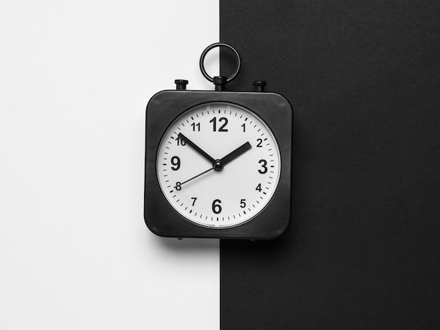 Klasyczny czarny zegarek z białą tarczą na czarno-białym tle. pokrętło krasowe.