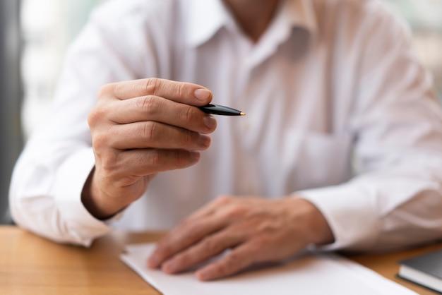 Klasyczny człowiek trzyma długopis widok z przodu