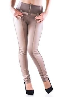 Klasyczny damski strój w jasnych, skórzanych spodniach i czarnych szpilkach