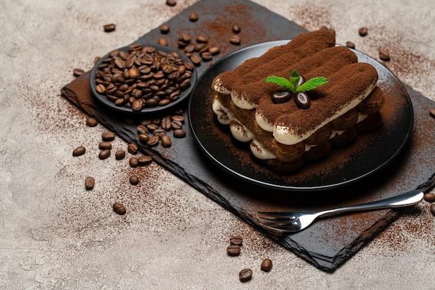 Klasyczny deser tiramisu na talerzu ceramicznym na betonie