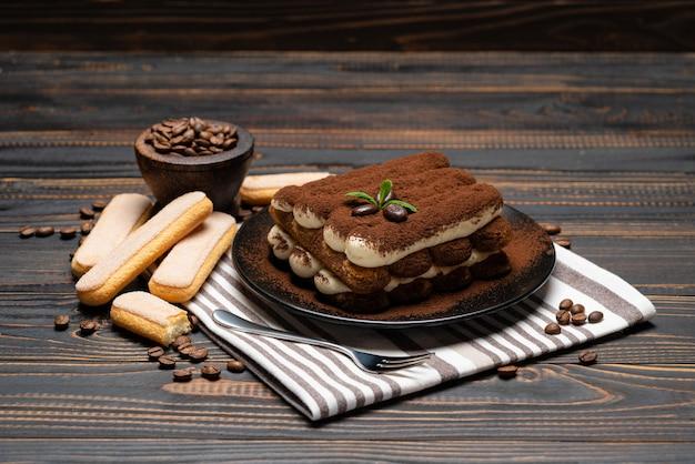 Klasyczny deser tiramisu na talerzu ceramicznym na drewnianej ścianie lub stole