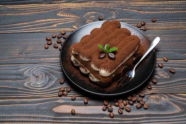 Klasyczny deser tiramisu na talerzu ceramicznym na drewnianym