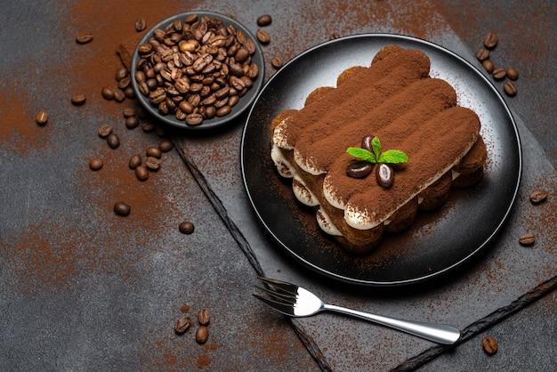 Klasyczny deser tiramisu na talerzu ceramicznym na powierzchni betonu