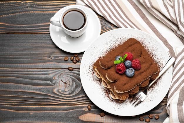 Klasyczny deser tiramisu z jagodami i filiżanką espresso