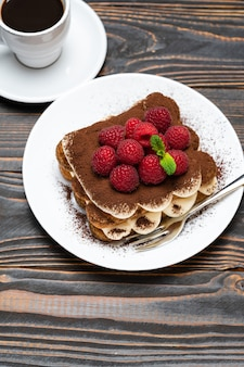 Klasyczny deser tiramisu z malinami i filiżanką espresso