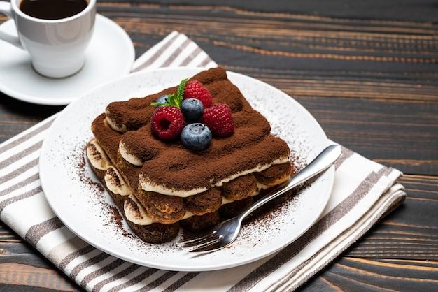 Klasyczny deser tiramisu z malinami i jagodami oraz filiżanką espresso