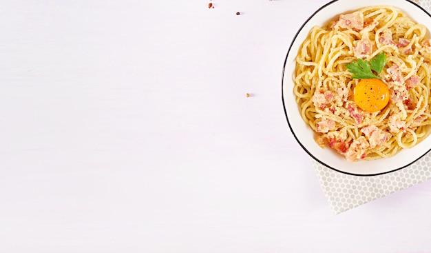 Klasyczny domowy makaron carbonara z pancettą, jajkiem, twardym parmezanem i sosem śmietanowym.