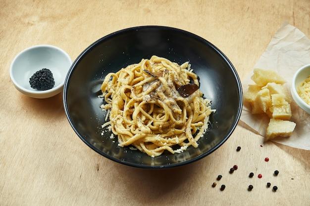 Klasyczny domowy makaron z czarną truflą, parmezanem i grzybami w czarnej misce. tradycyjna kuchnia włoska.