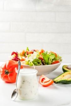 Klasyczny domowy sos sałatkowy ze świeżych warzyw na białym marmurowym stole