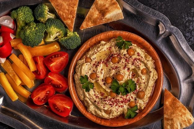 Klasyczny hummus z warzywami na talerzu i chlebkiem pita.